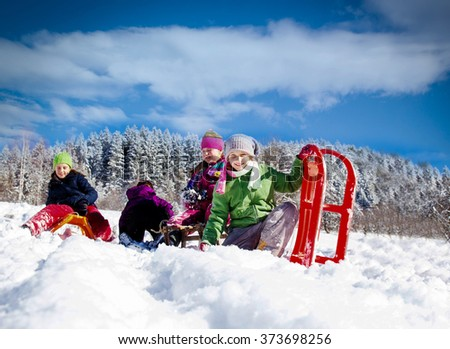 Happy children sledding at winter time. Group of children spending a nice time in winter.