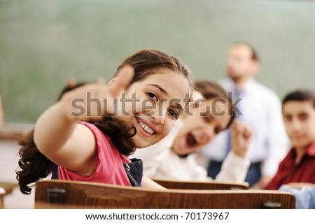 Happy children smiling and laughing in the classroom, showing thumb up, successful pupils and teacher - stock photo