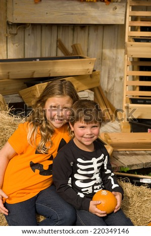 Happy children smiling wearing clothes for Halloween with pumpkins - stock photo