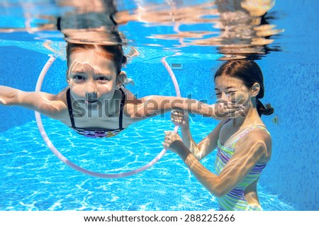 Happy children swim in pool underwater, girls swimming, playing and having fun, kids water sport