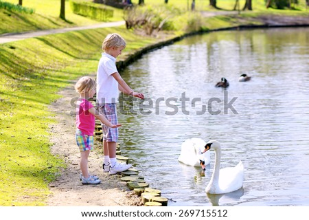 Happy children, teenage boy and his cute little sister enjoying warm sunny day playing in the park feeding hungry birds in the pond - stock photo