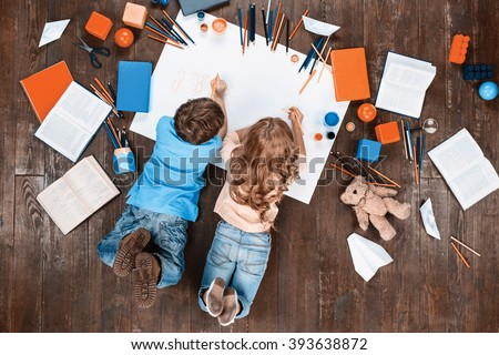 Happy children. Top view creative photo of little boy and girl on vintage brown wooden floor. Children lying near books and toys, and painting. Vintage colors - stock photo