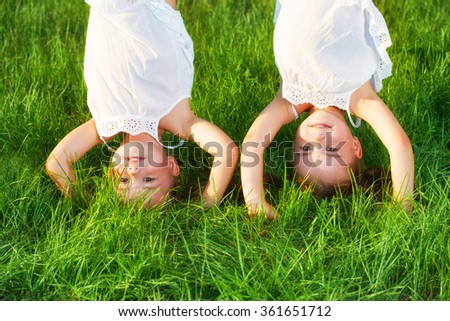 happy children twins sister upside down in the summer - stock photo