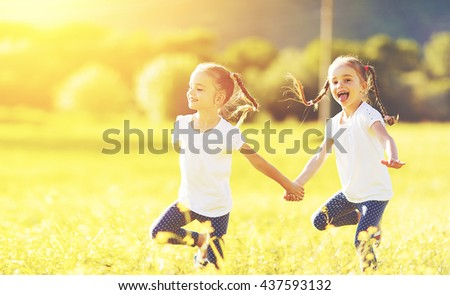 happy children twins sisters run and play outdoors on the meadow - stock photo