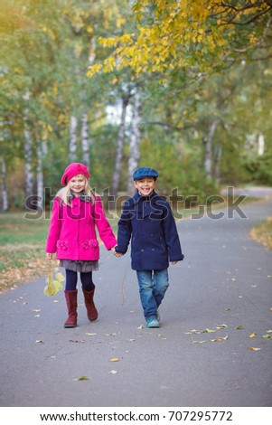 Happy children walking in beautiful autumn park on warm sunny fall day.