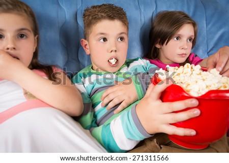 Happy children watching movie at home - stock photo