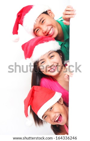 Happy Children wearing Santa Hat looking over from a white wall. - stock photo