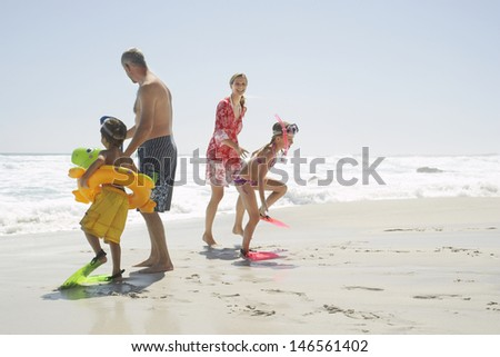 Happy children wearing scuba equipment while standing with parents at beach