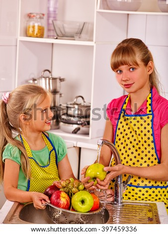 Happy children wering apron washing fruit at home kitchen. - stock photo