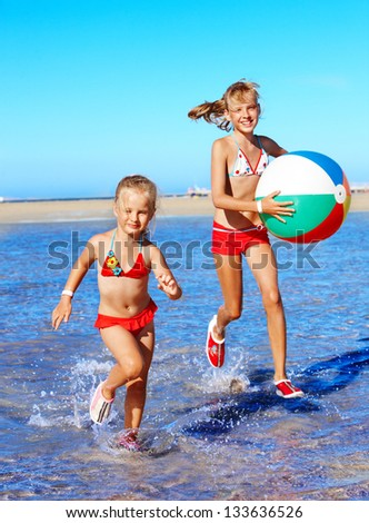 Happy children with beach ball running on  beach.
