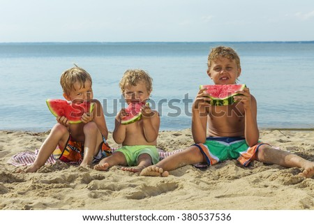 Happy children with big red slices of watermelon sitting on the beach. Healthy eating concept.