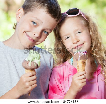 Happy children with ice cream outdoors - stock photo