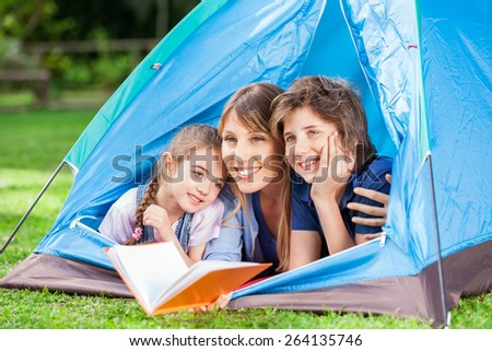 Happy children with mother holding book in tent at park - stock photo
