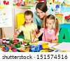 Happy children  with teacher painting. - stock photo