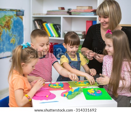 Happy children with teacher  playing with color play dough at classroom - stock photo