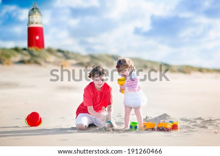 Happy children, young active boy and his adorable curly baby sister wearing a dress playing with sand toys on a sunny windy beach with a red lighthouse on Texel island, Holland, Netherlands - stock photo