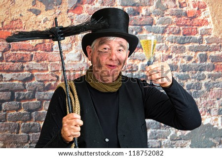 Happy chimney sweep toasting to the new year with a glass of champagne - stock photo