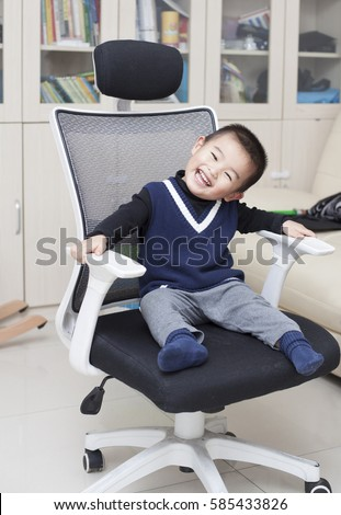 Happy Chinese baby boy sitting on a chair indoors, Beijing, China