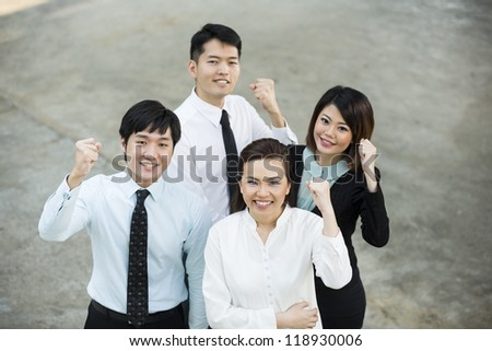 Happy Chinese Business colleagues looking up smiling & cheering. - stock photo