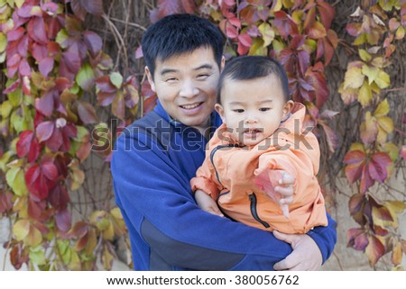 Happy Chinese father and son in front of Boston Ivy, shot in Beijing, China - stock photo