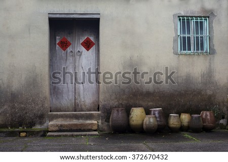 Happy Chinese lunar year . An old wooden door on grunge cement wall with Chinese lunar new year decoration and some urns in front of the wall.  The two Chinese character meaning good fortune. - stock photo
