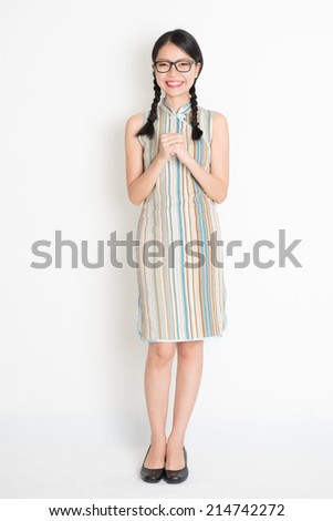 Happy Chinese New Year!! Portrait of Asian Chinese girl blessing, in traditional cheongsam standing on plain background.