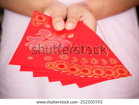 happy chinese new year, woman hand holding red envelope of gift chinese new year