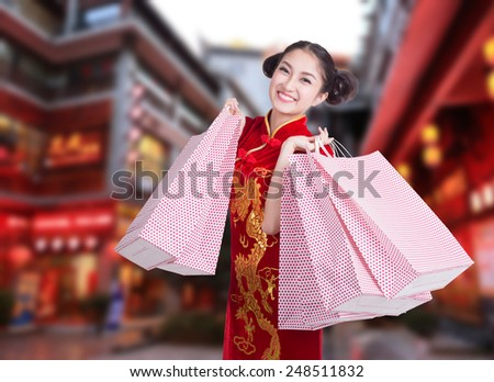 happy Chinese woman dress traditional cheongsam at street shopping - stock photo