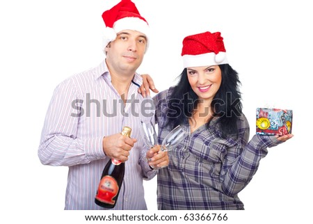 Happy Christmas couple in Santa hats holding a gift,champagne and glasses isolated on white background