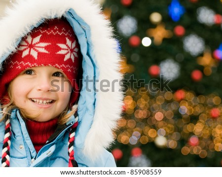 Happy Christmas - Little girl and Christmas tree (Defocused Christmas Tree Lights) - stock photo