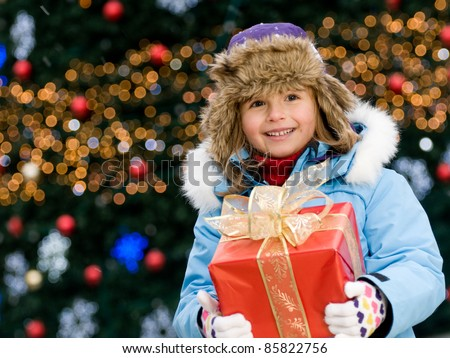 Happy Christmas - Little girl with Christmas gift  (Defocused Christmas Tree Lights) - stock photo