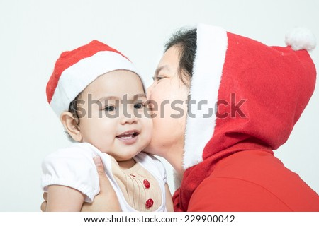 Happy Christmas mother kissing daughter on a white background - stock photo