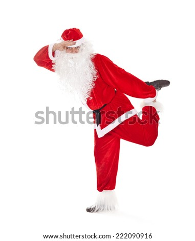 Happy Christmas Santa Claus having fun, standing on one leg and look far away, isolated on white background