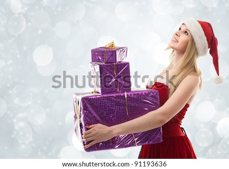 Happy Christmas woman holding gifts wearing Santa costume - stock photo