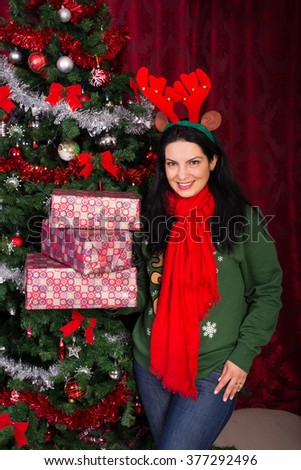 Happy Christmas woman standing near tree and holding presents home