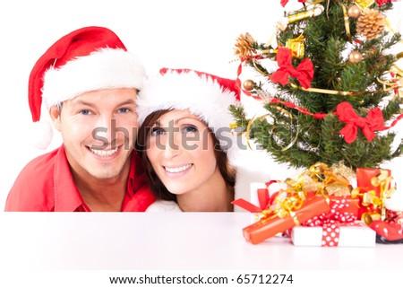 Happy christms couple smiling wearing santa hat - stock photo