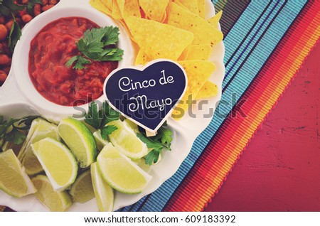 Happy Cinco de Mayo party table with food platter including limes, corn chips, chilli beans and salsa on a red wood background, with applied retro style filter.