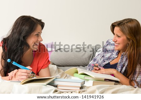 Happy classmates lying on bed and learning at dorm - stock photo