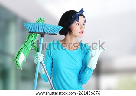 Happy cleaning woman showing copy space - stock photo