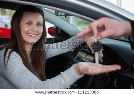 Happy client receiving car keys in a garage - stock photo