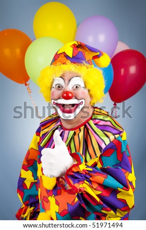 Happy clown with balloons giving thumbs up sign. - stock photo