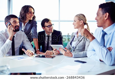 Happy co-workers discussing ideas in office - stock photo