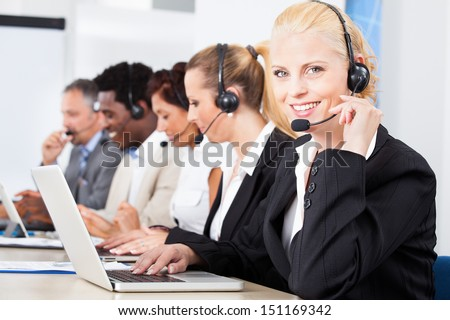 Happy Co-workers Wearing Headsets Working In Call Center - stock photo