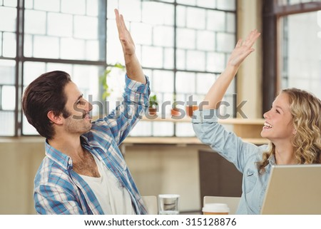 Happy colleagues giving high five while working at office - stock photo