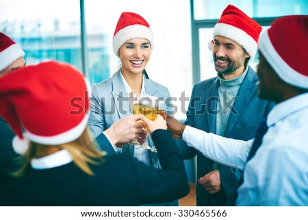 Happy colleagues in Santa caps toasting with champagne in office - stock photo