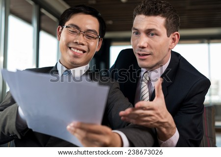 Happy colleagues reading report together - stock photo
