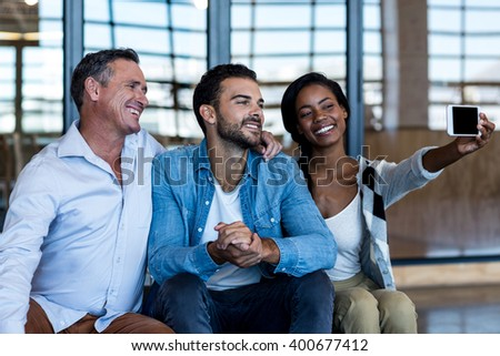 Happy colleagues taking selfie in the office - stock photo