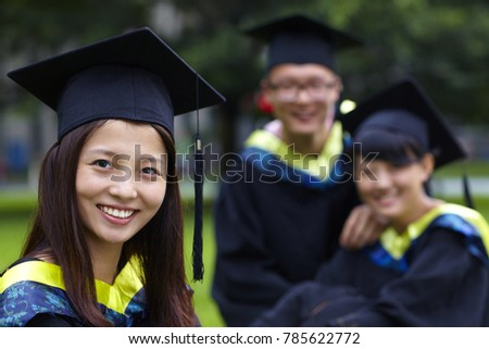 happy college graduates smile at camera