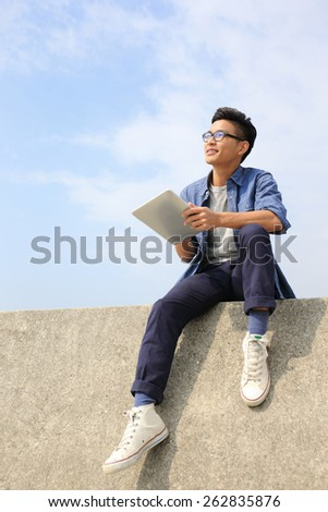 Happy College student man using digital tablet pc and look blue sky background, asian male - stock photo