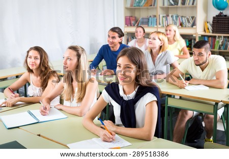 Happy college students sitting at their desks in auditorium and looking at their teacher